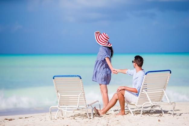 Junge paare auf weißem strand während der sommerferien Premium Fotos