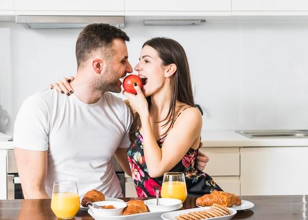 Junge paare, die apfel mit frühstück auf holztisch essen Kostenlose Fotos