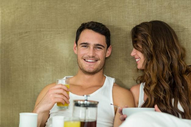 Junge paare, die auf bett im schlafzimmer frühstücken Premium Fotos