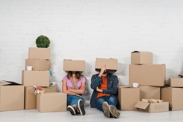 Junge paare, die auf boden mit ihrem kopf sitzen, der mit pappschachteln in ihrem neuen haus bedeckt wird Kostenlose Fotos