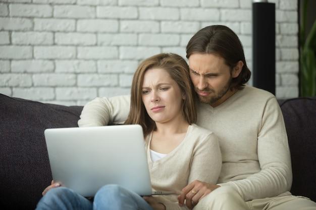 Junge paare, die auf dem laptop mit dem ekel schauen, der durch nachrichten verwirrt wird Kostenlose Fotos