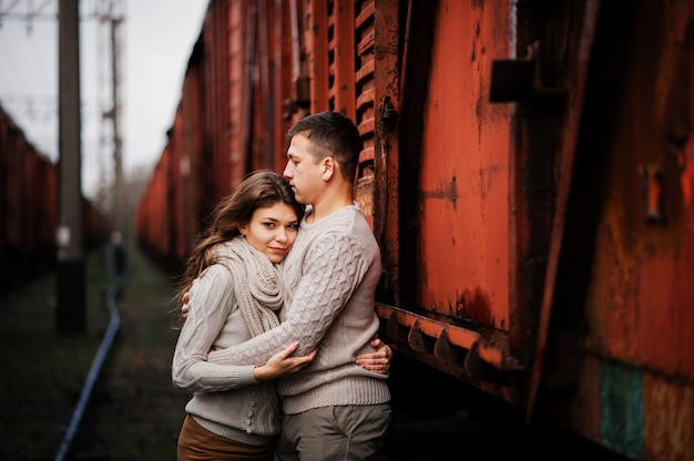 Junge paare, die auf den gebundenen warmen strickjacken umarmen in der liebe an den bahnhöfen tragen Premium Fotos