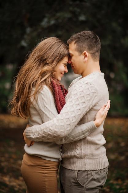 Junge paare, die auf den gebundenen warmen strickjacken umarmen in der liebe an der stadt in den herbsthintergrundgelbbüschen und -bäumen tragen. Premium Fotos