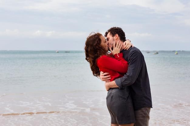 Junge paare, die auf sandigem seeufer küssen Kostenlose Fotos