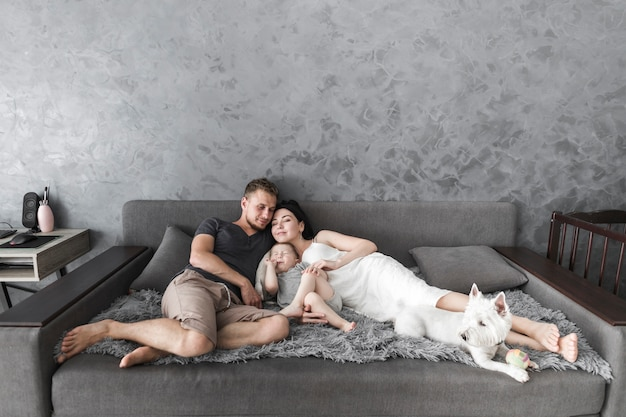 Junge paare, die auf sofa mit ihrem sohn und weißem hund sich entspannen Kostenlose Fotos