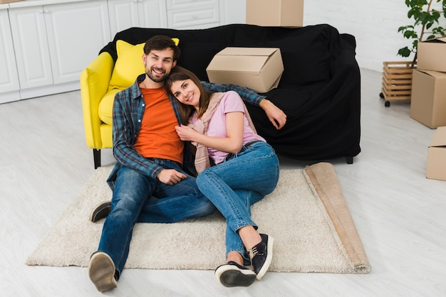 Junge paare, die auf teppich nahe dem sofa des neuen hauses sich entspannen Kostenlose Fotos