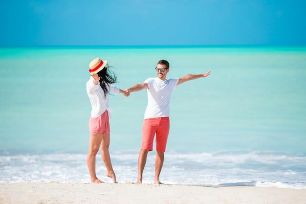Junge paare, die auf tropischen strand mit weißem sand- und türkisozeanwasser gehen Premium Fotos