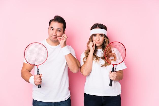 Junge paare, die das badminton lokalisiert mit den fingern auf den lippen halten ein geheimnis spielen. Premium Fotos