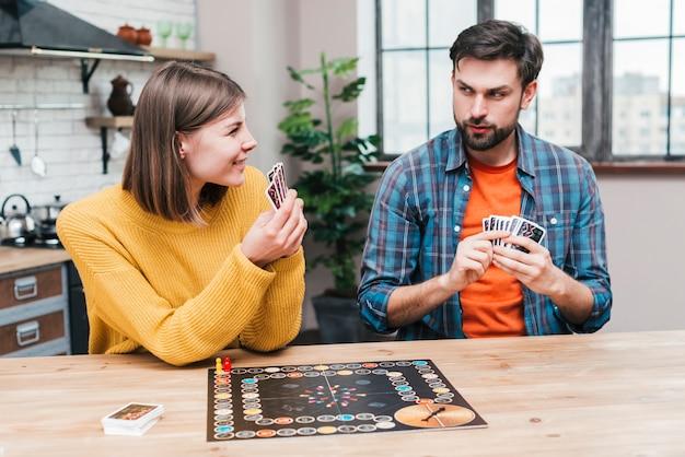Junge paare, die das brettspiel in der küche spielen Kostenlose Fotos