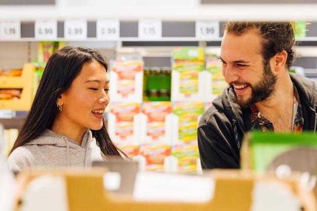 Junge paare, die das einkaufen im supermarkt tun Kostenlose Fotos