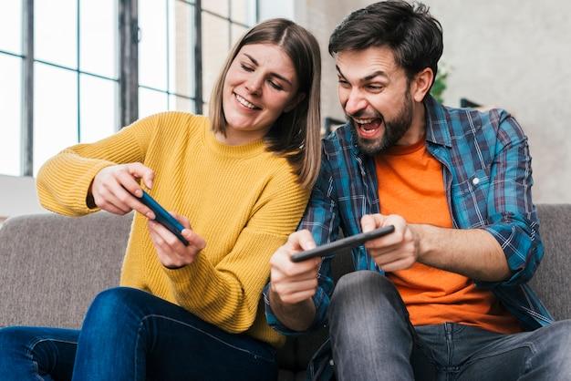 Junge paare, die das videospiel am handy spielen Kostenlose Fotos
