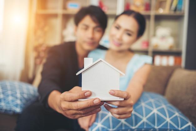 Junge paare, die ein weißes miniaturhaus im wohnzimmer halten Kostenlose Fotos