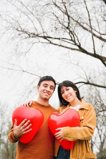 Junge paare, die geformte ballone des herzens umarmen und halten Kostenlose Fotos