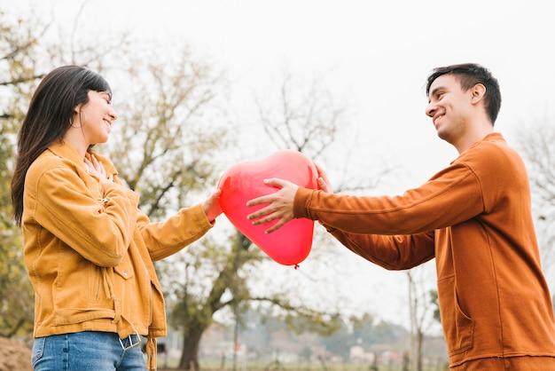 Junge paare, die geformten ballon des herzens halten Kostenlose Fotos