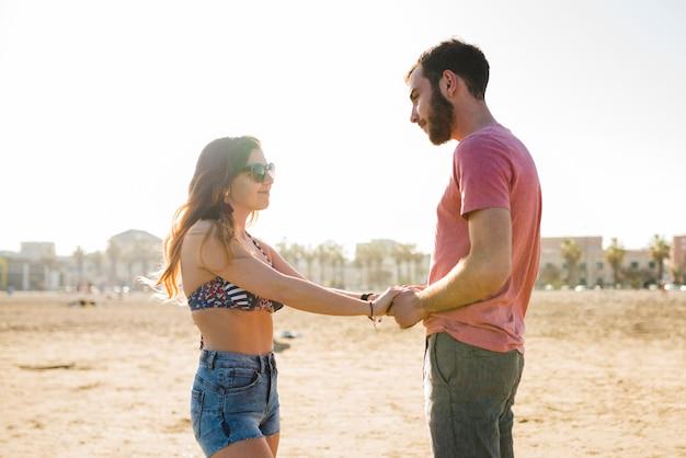 Junge paare, die hand des anderen stehen, die auf strand steht Kostenlose Fotos
