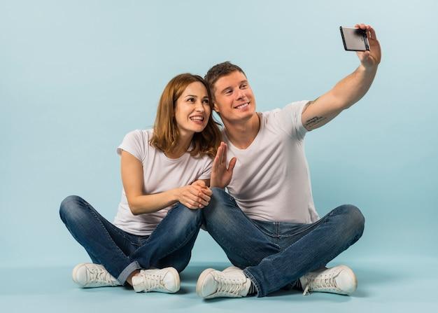 Junge paare, die ihre hand wellenartig bewegt, die selfie auf smartphone gegen blauen hintergrund nimmt Kostenlose Fotos