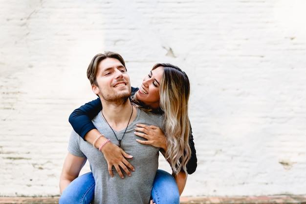 Junge paare, die ihre liebe mit lustigen küssen und liebkosungen feiern. Premium Fotos