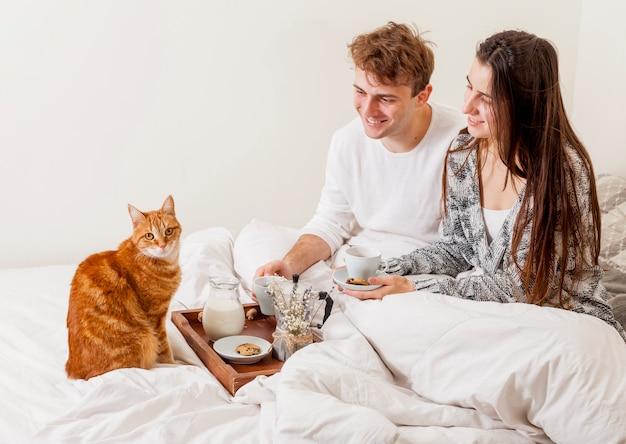 Junge paare, die im bett frühstücken Kostenlose Fotos