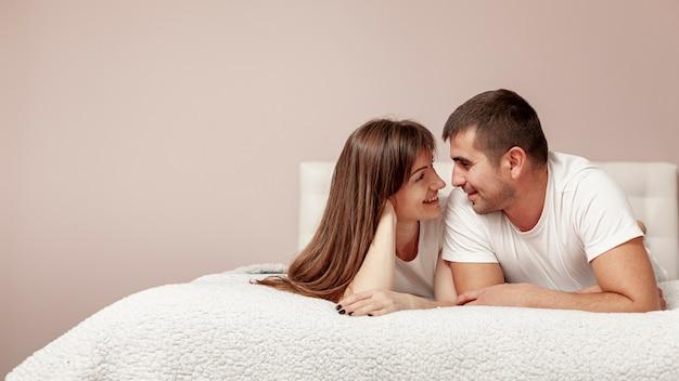 Junge paare, die im bett sitzen und einander betrachten Premium Fotos