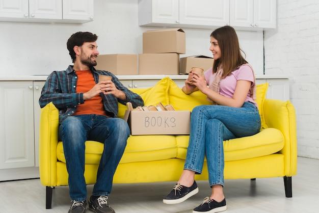 Junge paare, die in der hand auf dem gelben sofa hält tasse kaffee glas mit pappschachtel im wohnzimmer sitzen Kostenlose Fotos