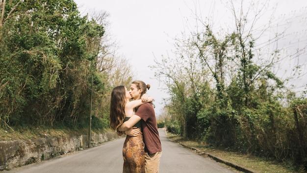 Junge paare, die in der mitte der straße küssen Kostenlose Fotos