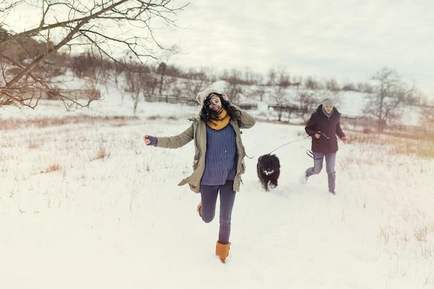 Junge paare, die mit einem hund an einem wintertag gehen Kostenlose Fotos