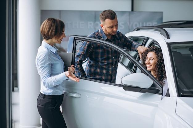 Junge paare, die mit einem verkäufer in einem autosalon sprechen Kostenlose Fotos