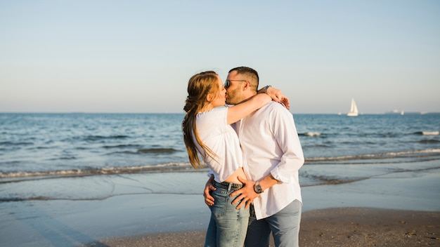 Junge paare, die nahe der küste am strand sich küssen Kostenlose Fotos