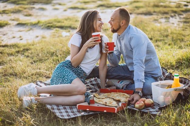 Junge paare, die picknick mit pizza im park essen Kostenlose Fotos