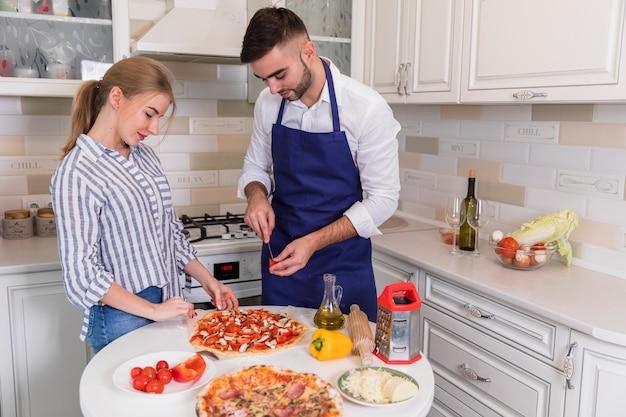 Junge paare, die pizza mit gemüse und pilzen kochen Kostenlose Fotos