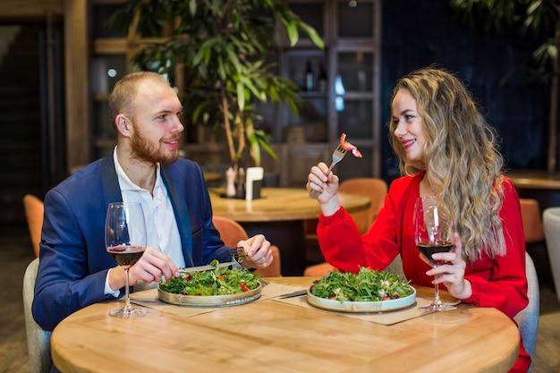 Junge paare, die salat im restaurant essen Kostenlose Fotos