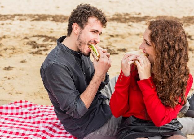 Junge paare, die sandwiche auf karierter bettdecke essen Kostenlose Fotos