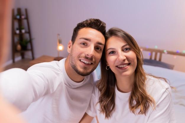 Junge paare, die selfie im schlafzimmer nehmen Kostenlose Fotos