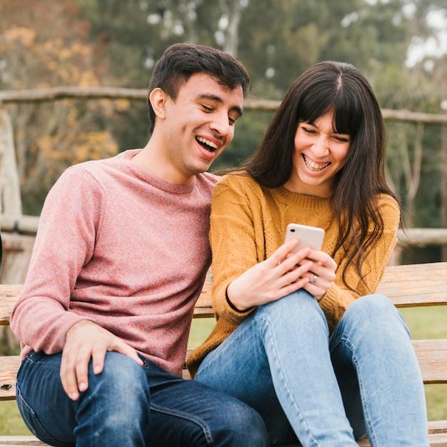 Junge paare, die smartphoneschirm betrachtend lachen Kostenlose Fotos