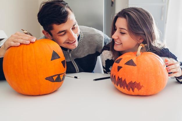 Junge paare, die steckfassung-olaterne für halloween auf küche bilden. mann und frau, die ihre kürbise vergleichen Premium Fotos