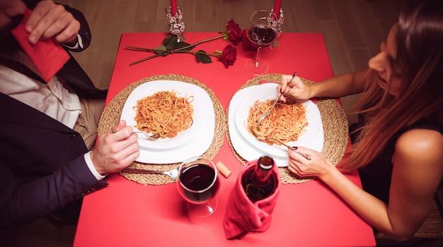 Junge paare, die teigwaren am festlichen tisch essen Kostenlose Fotos