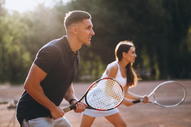 Junge paare, die tennis am gericht spielen Kostenlose Fotos