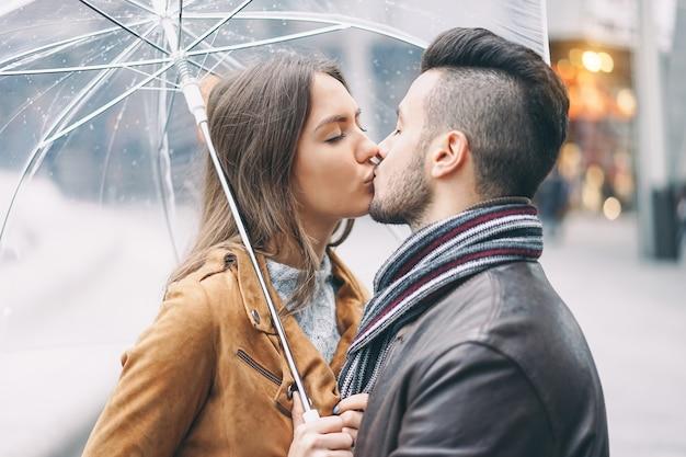 Junge paare, die unter regenschirm am regnerischen tag im stadtzentrum küssen Premium Fotos