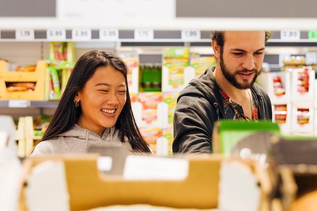 Junge paare, die waren im supermarkt wählen Kostenlose Fotos