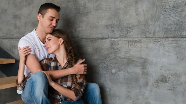 Junge paare, die zu hause auf schritten umarmen Kostenlose Fotos