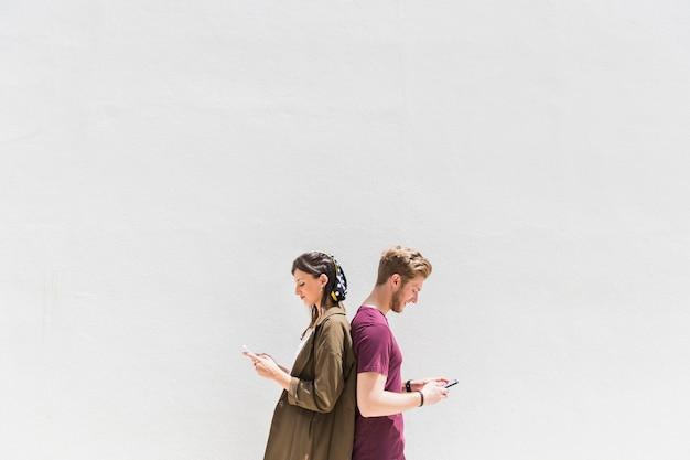 Junge paare, die zurück zu rückseite unter verwendung des mobiltelefons stehen Kostenlose Fotos