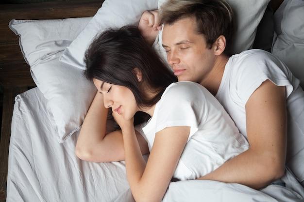 Junge paare, die zusammen schlafen auf bequemem bett schlafend schlafen Kostenlose Fotos
