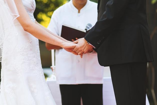 Junge paare halten hand an der hochzeitszeremonie Premium Fotos