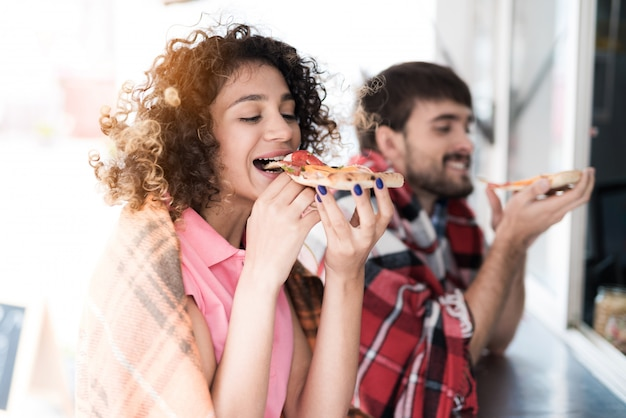 Junge paare in den karierten plaids pizza essend. Premium Fotos