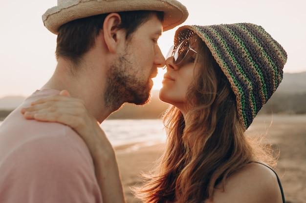 Junge paare in der liebe, die auf dem strand, sonnenuntergangozean genießend steht. Kostenlose Fotos