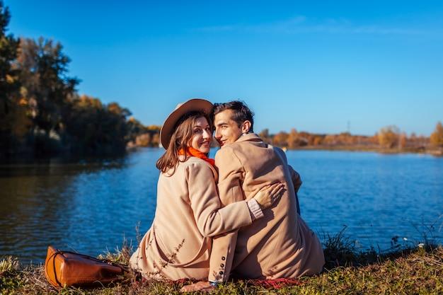 Junge paare in der liebe, die durch herbstsee kühlt. glücklicher mann und frau, die natur und das umarmen genießt Premium Fotos