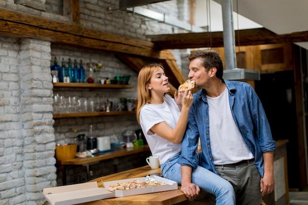 Junge paare in der liebe, die pizza im rustikalen haus isst Premium Fotos