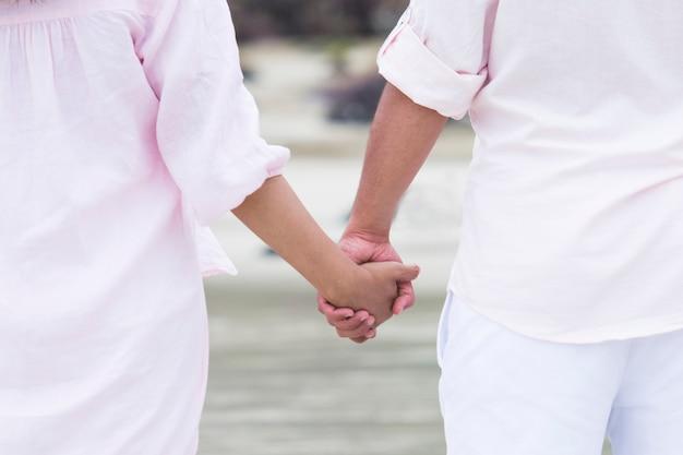 Junge paare in der liebe, die zusammen in das seehändchenhalten im süßen kleid der paare geht. Premium Fotos