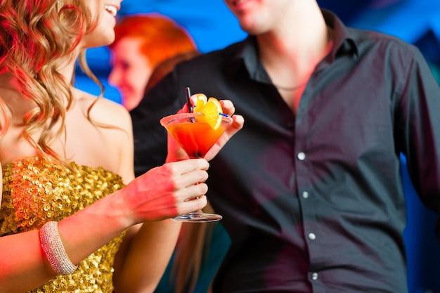 Junge paare in trinkenden cocktails der bar oder des vereins Premium Fotos