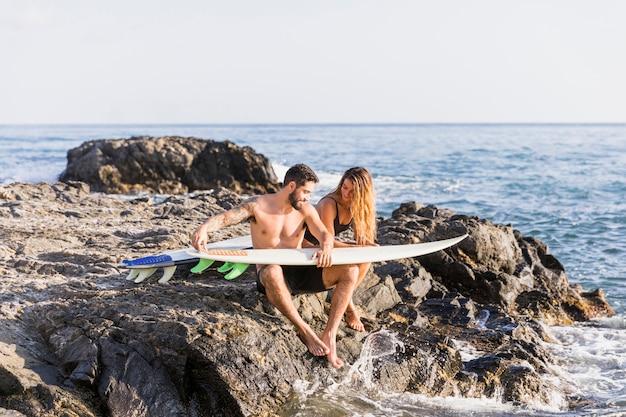 Junge paare mit den surfbrettern, die auf steinigem ufer sitzen Kostenlose Fotos
